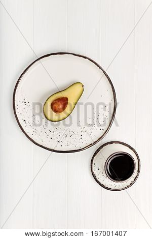 Goof for your body. Balanced vegetable breakfast consisting of avocado and a cup of coffee being served on white clay plates which are standing on a white table