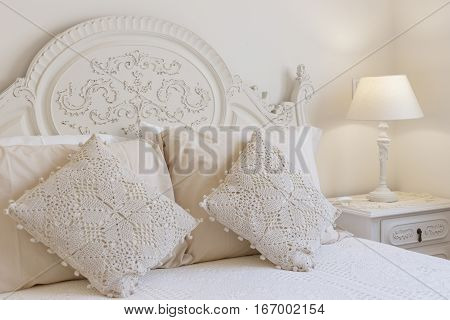 Detail of a bed and nightstand with crochet pillows