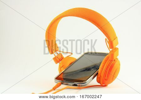 Orange headphones and mobile phone with a scratched screen