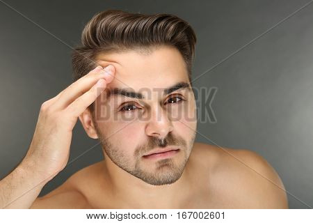 Young handsome man examining his face on grey background
