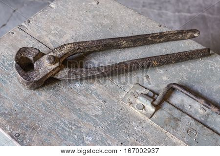 pincers over old tools for housework, vintage look, over old wooden toolbox, timeworn paint