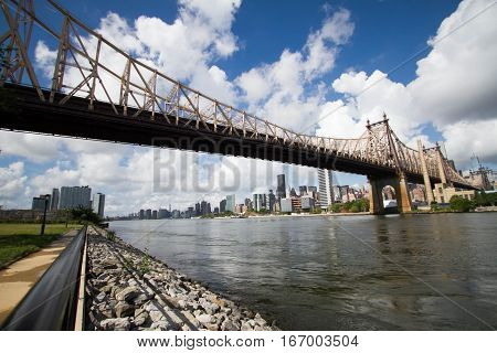 Queensboro bridge over river and shore with cloudy sky