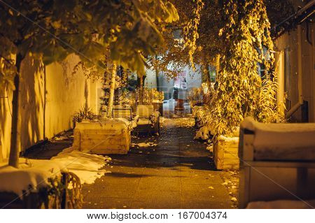 Cosy courtyard covered by first snow. Night scene selective focus