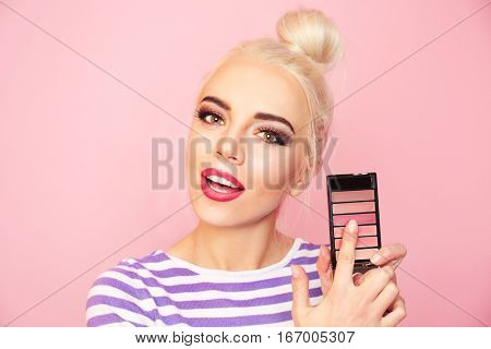 Portrait of beautiful young woman holding blusher