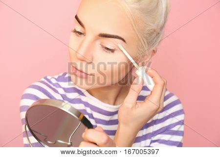 Beautiful young woman applying concealer on eyelid