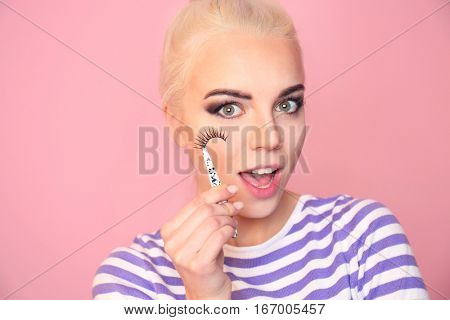 Beautiful young woman with fake eyelashes on pink background