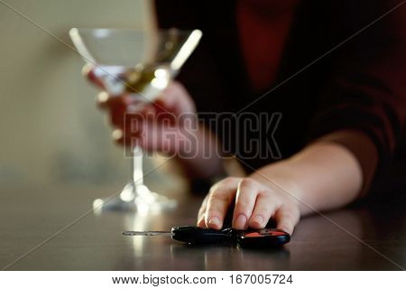 Woman with car key and glass of alcoholic beverage, closeup. Don't drink and drive concept