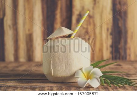 Coconut with plumeria on wooden background