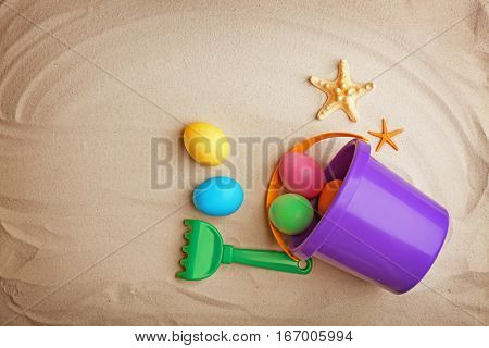 Easter eggs with pail and rake on sand