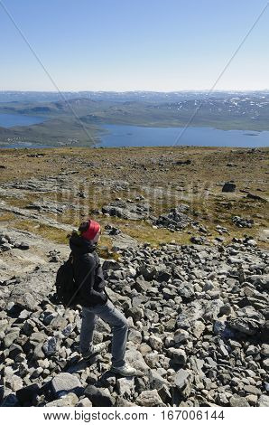 Girl wearing hiking clothes walking a hiking path on the top of Saana Fell Kilpisjarvi Finnish Lapland Finland Europe. Lake Kilpisjarvi in the background