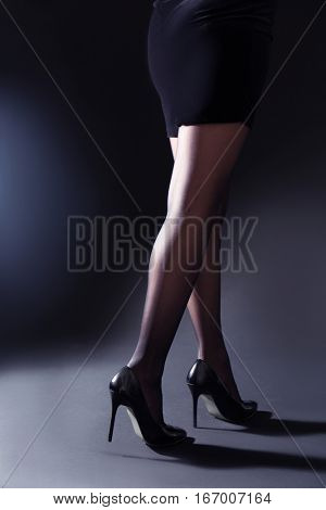 Beautiful woman legs in black tights on grey background