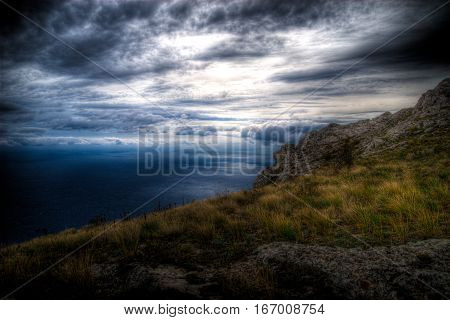 Dark blue clouds before the storm, and the clouds in the mountains, the view from the mountains to the sea and the sky with blue clouds, storm at sea, the mountain slope