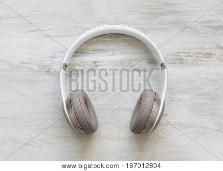 Headphones on wooden floor background from top