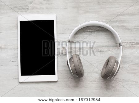 Headphones and tablet on wooden floor from above