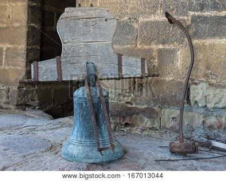 Bronze rusty bells with its counterweight yoke and hammer. Bell tower on the church Late Gothic building