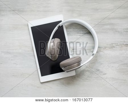 Headphones and tablet on wooden floor background
