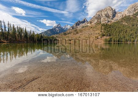 a scenic fall reflection of the Tetons in String Lake Teton National Park
