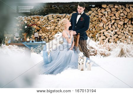 Winter wedding outdoor on snow and firewood background. Bride sits on a chair groom stands close by. Beside them is table with goblets of wine and bouquet.