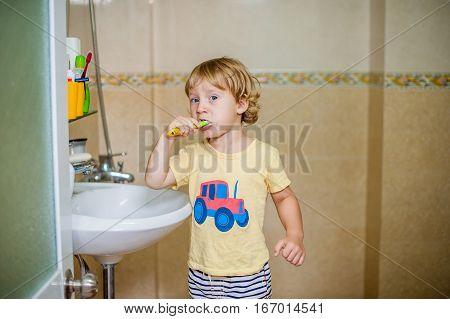 Little Boy Brushing His Teeth In The Bathroom