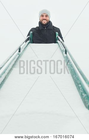 Young man at the top of the slide in the playground in the winter