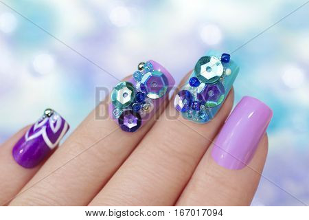 Multicolored purple blue manicure with design on nails with glitter and rhinestones of different shapes and colors closeup on female hand.