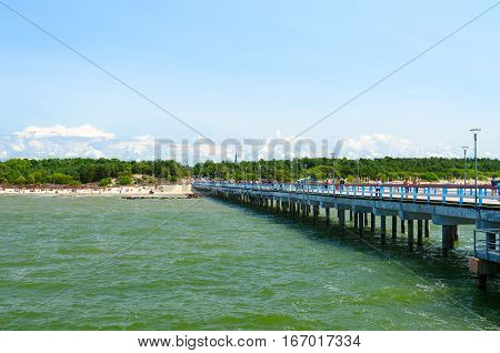 PALANGA LITHUANIA - JULY 12 2015: Unidentified people walk on long pier and rest on beach in popular resort town of Palanga Lithuania