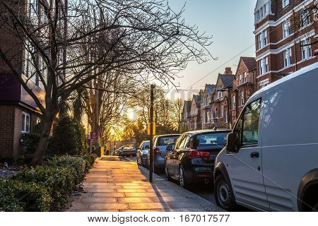 Beautiful picture of the sunset in London suburbs taken in the side walk with trees cars and tipical flats showing