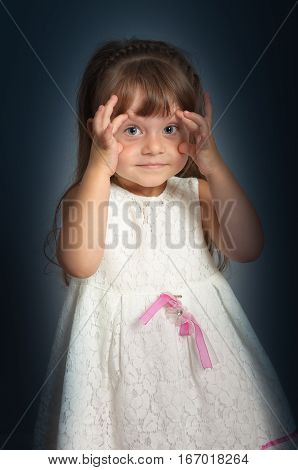 Cute little girl in a white dress opened her eyes wide with his hands. Studio photography on a dark background