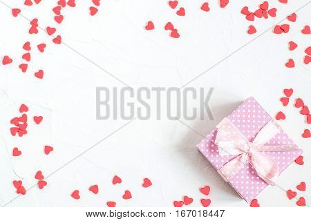 Elegant festive background with decorations in the form of heart and gift box with bow on white textured surface with space for text. The mood of tenderness and love. Symbols of Valentines Day