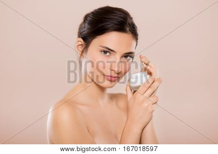 Beautiful woman holding jar of skin cream for face and body isolated on pink background. Young woman applying cosmetic moisturizer and looking at camera. Girl showing small jar of moisturizing lotion.