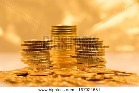 Gold Eagle one ounce coins stacked into larger columns against a golden background and reflecting