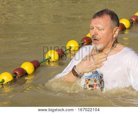 BETHABARA, JORDAN - JANUARY - 11, 2017: Man middle-aged pilgrim passes in the River Jordan Baptism in the Jordan. JORDAN - 2017