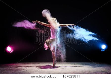 Woman in beige body and her hair loose posing on a tiptoe in cloud of pink and yellow dust streching her arms gracefully