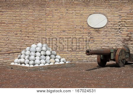 Some antique cannon with white stone cannonballs