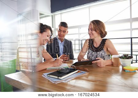 Candid photo of a corporate businesspeople group discussing strategies in professionnal indoors setting.