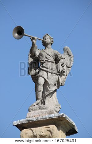 Statue of angel playing the horn symbol of the power of god