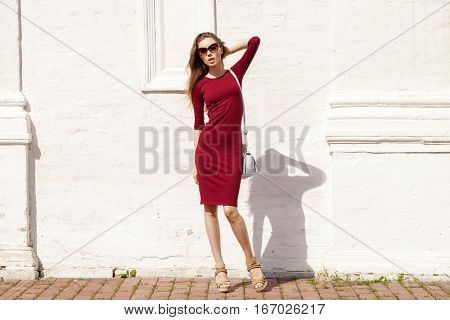 Portrait in full growth, Beautiful young brunette woman in red dress, against white wall, summer outdoors