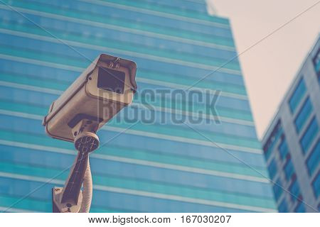 Security camera (CCTV) for safety on blue sky and city background process in vintage style