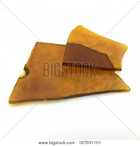 Marijuana shatter (concentrate) isolated on white background.