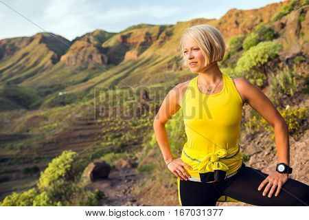 Young woman relaxing and running on beautiful mountain trail at sunset summer day. Female runner training and working out jogging and exercising outdoors in nature Canary Islands Spain.
