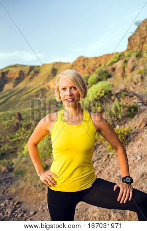 Young woman relaxing and running on beautiful mountain trail at sunset summer day. Female runner portrait training and working out jogging and exercising outdoors in nature Canary Islands Spain.