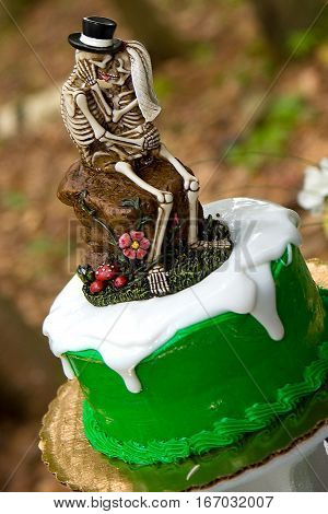 A cake topper of a skeleton bride and groom