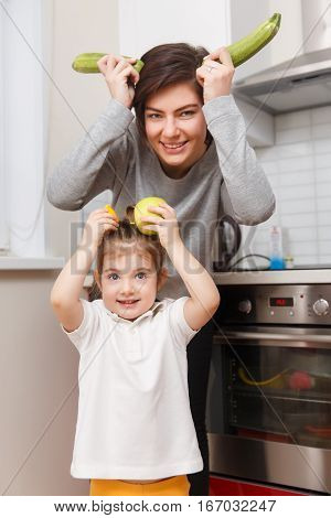 Mother and daughter with vegetables and fruits in joke kitchen