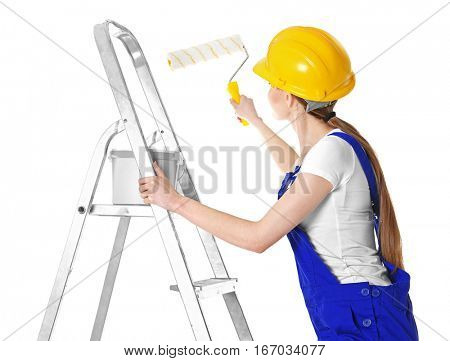 Beautiful young decorator on ladder against white background