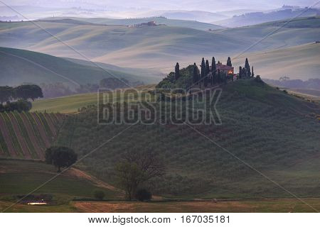 Farmhouse in the morning fog at the break of dawn in Tuscany between the rolling hills of the Val d'Orcia valley between Pienza and San Quirico d'Orcia in Italy.