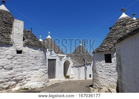 Traditional white plaster trulli houses with stone tiles in conical roofs in a small street in the town Alberobello Itria Valley in Puglia Italy.
