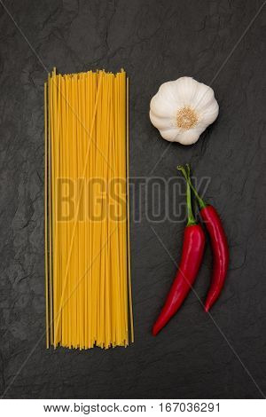ingredients for spaghetti aglio e olio on black slate background: spaghetti, garlic and red pepper