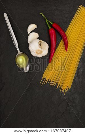 ingredients for spaghetti aglio e olio on black slate stone background