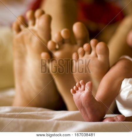 cute newborn foot with family members focus is tight on the newborn