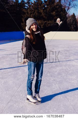 Cute Girl Is Going Skate Outdoors.girl In Winter Clothes Skating On Ice Rink.young Woman Skating On